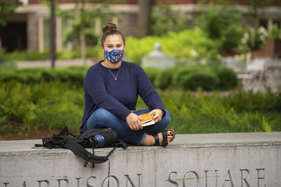 A Georgia Tech student outside on campus wearing a mask