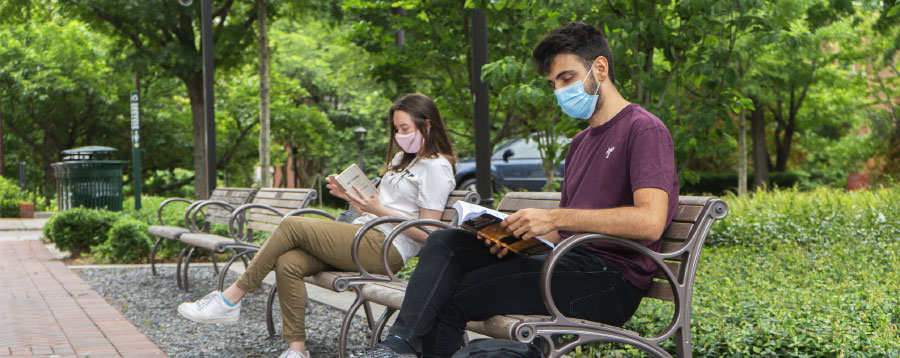 Georgia Tech students sitting on benches on campus and wearing face masks