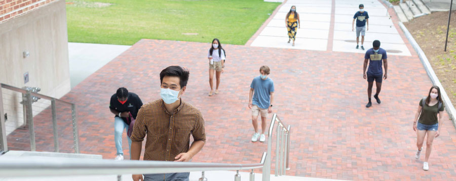 students socially distancing and wearing face masks approaching an on-campus facility